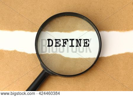 The Magnifying Glass Reveals The Define Text Appearing Behind The Torn Brown Paper. Business Concept