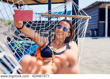 Woman on beach with cell phone. Woman taking selfie with cell phone on beach . Woman looking to cell phone in vacation. Cell phone photo selfie. Mobile phone selfie. Social.