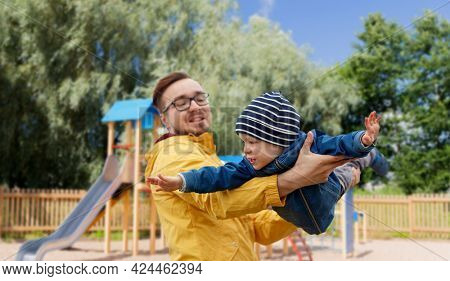 family, childhood, fatherhood, leisure and people concept - happy father and little son playing and having fun over children's playground background