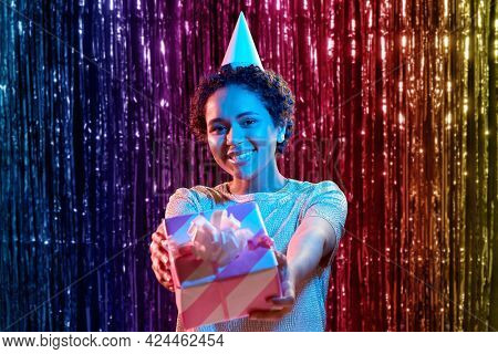 birthday, celebration and nightlife concept - happy smiling young african american woman in party cap with gift box over ultraviolet neon lights on rainbow foil curtain background