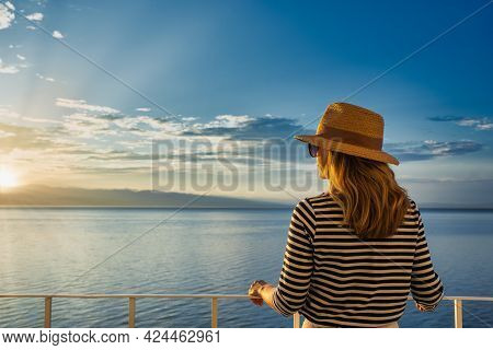 Shot Of Woman Wearing Straw Hat And Sunglasses While Standing On Balcony And Looking At Sea View. Da