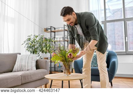 household, home improvement and interior concept - happy smiling young man placing flowers in vase on coffee table