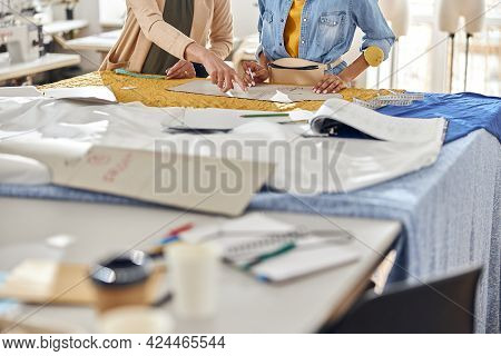 Mature Dressmakerteaches African-american Stagist To Draw Patterns On Fabric In Workshop, Closeup