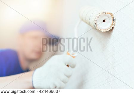 A Painter In A Cap And Gloves Paints The Wall With A Paint Roller. Portrait Of A Young Worker In Uni