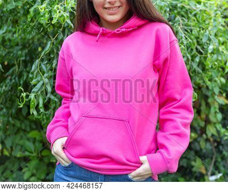 The smiling woman is wearing a pink hoodie, facing the camera outside. There is a blank space on the hoodie for a logo, design or text that may allude to a breast cancer awareness campaign.
