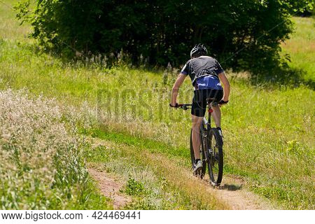 Summer Bike Ride In Nature. A Cyclist Rides On A Country Road. Selective Focus.