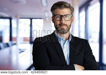Portrait Of Handsome Businessman Wearing Shirt And Suit While Standing At The Conference Room.