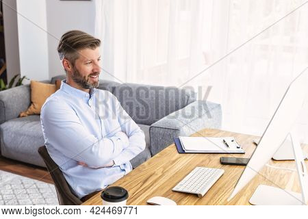 Shot Of Businessman Sitting Behind His Computer And Having Discussion And Online Meeting In Video Ca