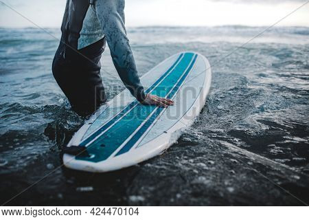 Man at the beach with his surfboard