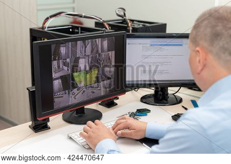 Side View Of Security Guard Monitoring Cctv Camera In Security Room. Surveillance, Control, Safety O