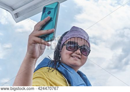 Young Pretty Asian Woman In Sunglasses And Life Jacket Taking A Selfie On Boat Trip And Smiling Agai
