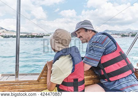 An Asian Boy In Panama, Life Jacket And Older Man, His Grandfather, Trip On Pleasure Boat On The Sea