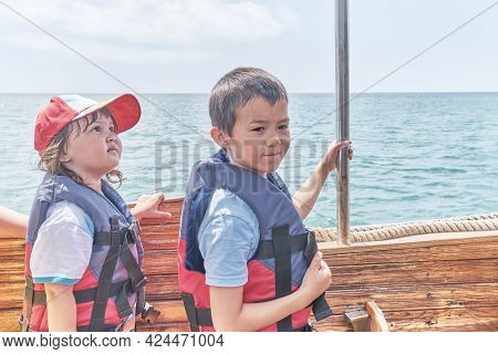 An Asian Little Girl And Boy, Her Brother, Both In Life Jackets Trip On Pleasure Boat On The Sea. Tr
