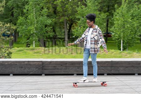 Skateboarding And Urban Lifestyle: Trendy African American Female Riding Longboard Dressed In City S