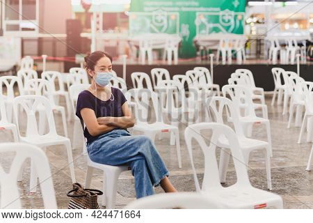 Asian Woman In Protective Mask Sitting On Chairs Waiting For Vaccination Against Covid-19