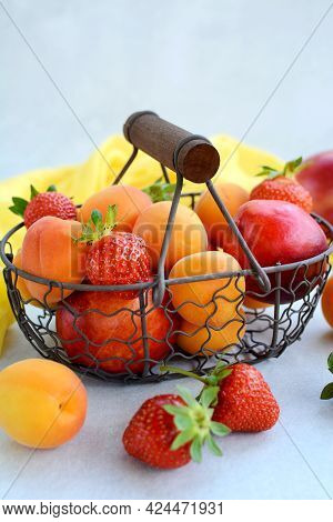A Vertical View Of Ripe Fruits And Berries - Strawberries, Peaches, Apricots In A Basket On A Light