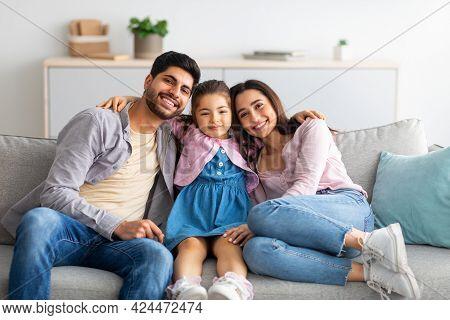 Family Home Leisure. Happy Eastern Parents And Their Cute Daughter Relaxing On Couch Together And Sm
