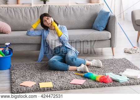Tired Woman Talking On Phone During Cleanup