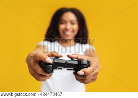 New Videogame Advertisement Concept. Overjoyed African American Woman Holding Game Controller, Yello