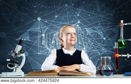 Smiling Schoolgirl Sitting At Desk With Open Book. Happy Girl Scientist Studying In Classroom. Chemi