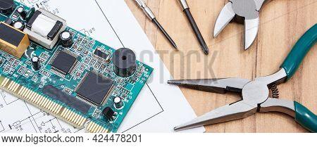 Printed Circuit Board With Transistors, Resistors, Capacitor. Precision Tools And Diagram Of Electro