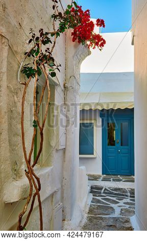 Romantic Traditional Alleyway Of Greek Island Towns. Whitewashed Walls, Blue Doors And Sky, Pink Bou