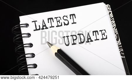 Latest Update Written Text In Small Notebook On Black Background