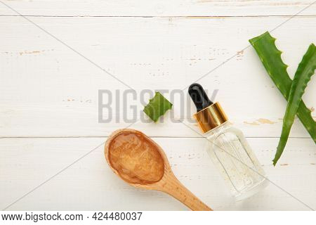 Aloe Vera Gel On Wooden Spoon With Aloe Vera And Oil Bottle On White Background. Top View.