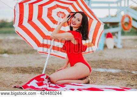 Beautiful Young Brunette Woman With Red Lips And Bikini Posing With Red And White Stripped Sun Umbre