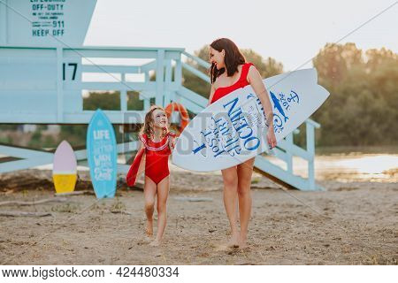 Beautiful Mother And Cute Daughter In Red Bikini Holding Surfboard And Walking On The Sand Beach Aga