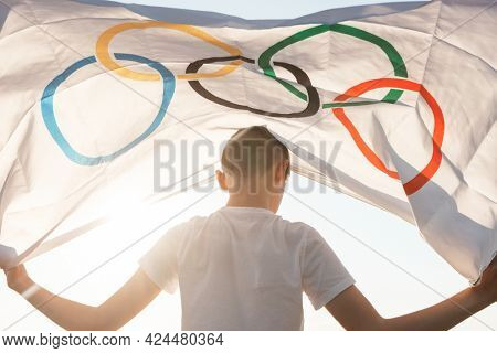 Portrait of boy waving flag the Olympic Games outdoors over cloudy sunset sky. Children sports fan. Summer olympic games concept. 08.06.2021, Barnaul Russia.