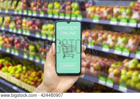 Online Grocery Delivery App In A Mobile Phone. Food Market Service In Smartphone With Shopping Cart.
