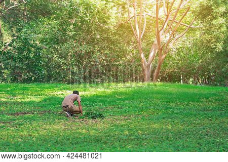Back View Of Asian Man Sits To Searching For A Lost Wallet On Grass In A Park. Man Sits Worried And