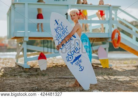 Cute Blond Teen Boy In Red Headband Posing With White Surfboard Against Lifeguard Tower On The Beach