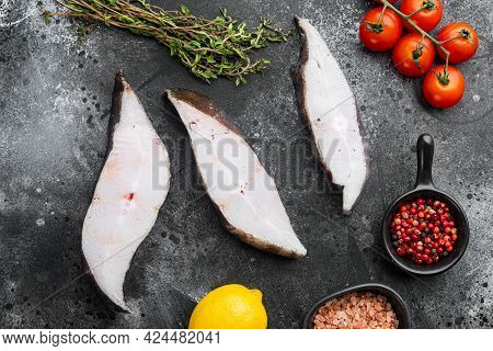 Raw Fresh Halibut Fish Steak Set, With Ingredients And Rosemary Herbs, On Black Dark Stone Table Bac