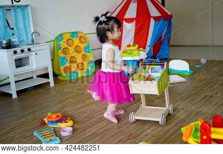 Happy Baby Girl Playing With Toys In Playroom With Her Shoping Cart And Cooking Toys At School No Te
