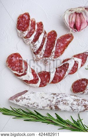 Dry Cured Fuet Salami Sausage Slices With Herbs On White Textured Background.