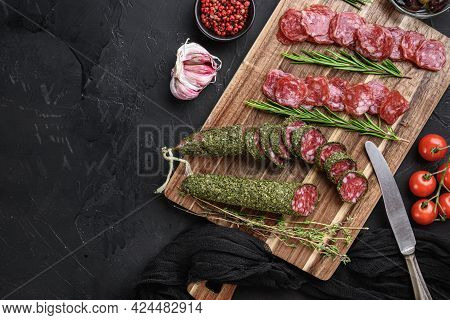 Spanish Fuet Salami Sausage Slices  On Black Textured Background With Space For Text.