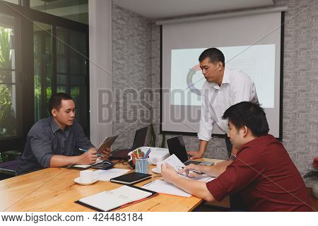 Business Team Meeting And Discussing Project Plan. Businessmen Discussing Together In Meeting Room.