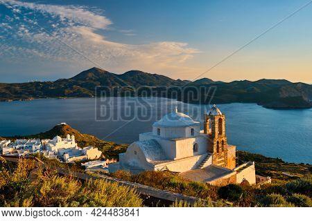 Traditional whitewashed Greek Orthodox church in Plaka village on Milos island on sunset. Milos island, Greece