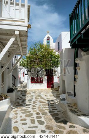 Picturesque scenic narrow Greek streets with traditional whitewashed houses with blue doors windows of Mykonos town and orthodox church in famous tourist attraction Mykonos island, Greece