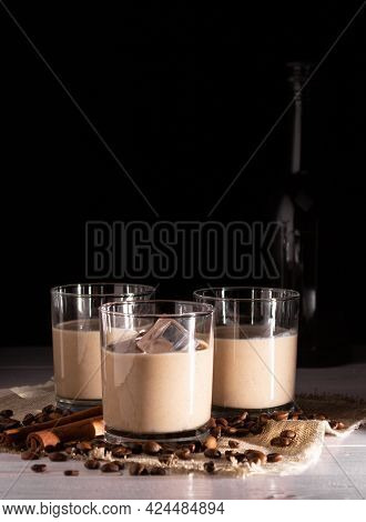 Glasses With Cream Liqueur And Ice. Coffee Beans, Black Bottle In The Background.