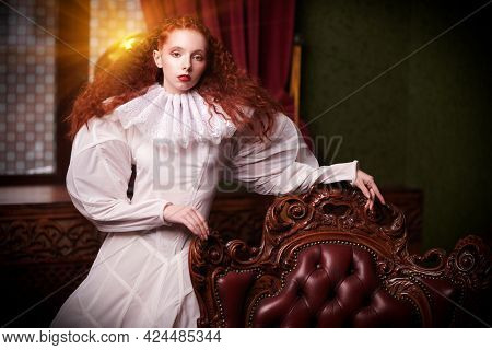History of fashion and hairstyles. A stylish fashion model girl with lush red hair with fine curls poses by a vintage armchair in art dress with a ruffled renaissance collar.