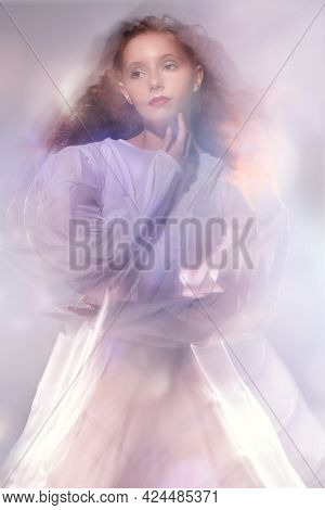 Art of fashion. Portrait of a tender girl with lush red curly hair posing in a long white haute couture dress among flashes and light haze. Studio shot.