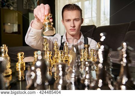 Strategic decision in business. Well-groomed smart man in elegant clothes plays chess in a modern luxury interior.