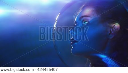 Beautiful tender girl with blue eyes in a glass spacesuit looks into the distance against the background of outer space. Space concept. Copy space.