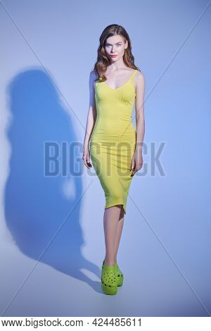 Full length portrait of a beautiful blonde girl in elegant yellow tight-fitting dress and sabot. Fashion studio shot.