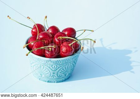 A Blue Ceramic Bowl Full Of Fresh And Juicy Cherries On A Pastel Background. Copy Space. Seasonal Su