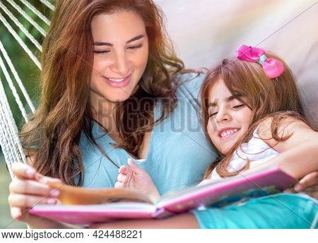 Portrait of a Happy Little Girl with Mother in the Hammock Reading Book. With Pleasure Spending Sunny Day on Backyard Together. Happy Summer Holidays.