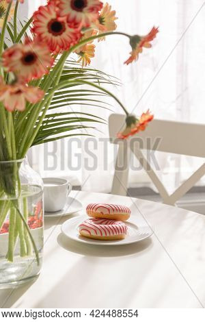 Romantic Breakfast In The Kitchen With A Bouquet Of Flowers, Donuts, Coffee And Fresh Strawberries.